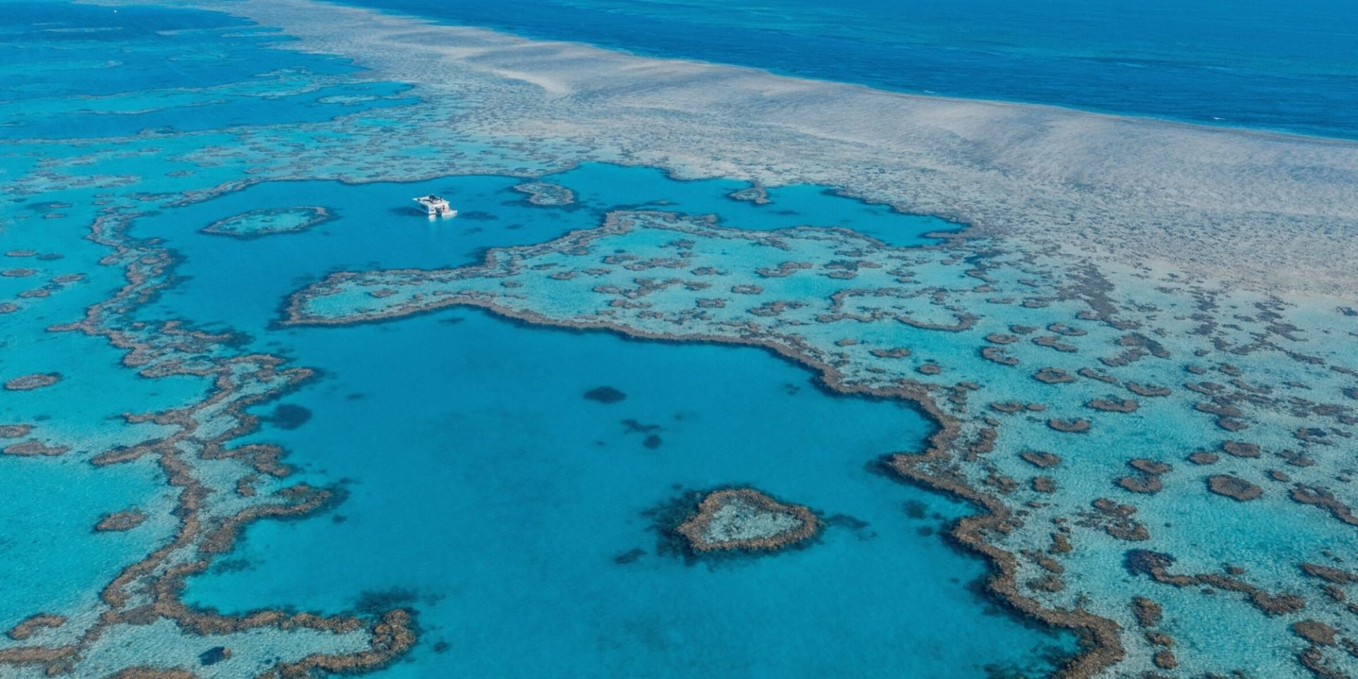 Image of the Great Barrier Reef. Bright blue waters and pale brown reefs